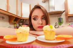 Woman with tape measure and cake. Diet dilemma. Royalty Free Stock Image