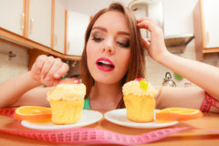 Woman with tape measure and cake. Diet dilemma. Stock Photos