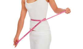 Woman with a tape measure measuring her waist Royalty Free Stock Photos
