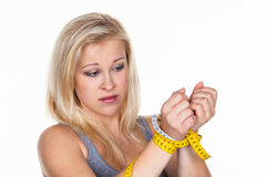 Woman with tape measure before the next diet. A young woman with a tape measure before the next diet. removing fast and Royalty Free Stock Image