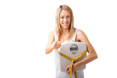 Woman with tape measure and weight scale showing thumbs up Royalty Free Stock Photography