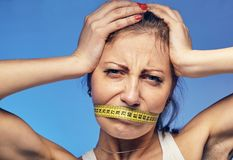 Woman with a taped tape on the lips. She is worried about the diet. A young woman with a taped tape on the lips. She is worried about the diet Royalty Free Stock Photography