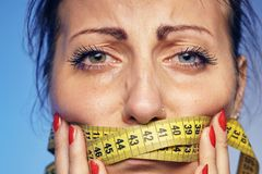 Woman with a taped tape on the lips. She is worried about the diet. A young woman with a taped tape on the lips. She is worried about the diet Stock Photo