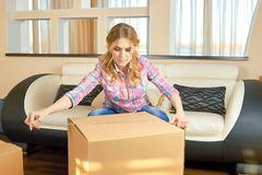 Woman taping cardboard box. Person in the room, relocation Royalty Free Stock Photo