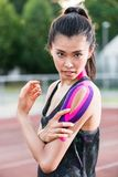 Woman taping with therapeutic tape on cinder track of sports sta. Dium Stock Photography