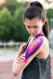 Woman taping with therapeutic tape on cinder track of sports sta. Dium Stock Photo