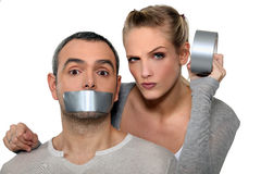 Woman taping-up boyfriend's mouth Royalty Free Stock Photos