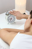 Woman tapping an alarm clock Stock Photo