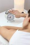 Woman tapping an alarm clock Stock Photo