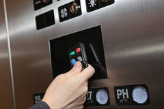 Woman tapping key fob. Inside elevator Royalty Free Stock Photos