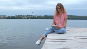 Woman tapping at tablet while sitting near lake in slow motion stock video footage