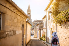Woman tarveling in Saint Emilion village, France. Young woman tourist walking old street at the famous Saint Emilion village in Bordeaux region in France stock photo