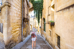 Woman tarveling in Saint Emilion village, France. Young woman tourist walking old street at the famous Saint Emilion village in Bordeaux region in France stock photography