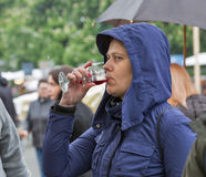 Woman taste wine during Kyiv Food and Wine Festival, Ukraine. Unrecognized woman with a hood taste wine during Kyiv Food and Wine Festival in National Royalty Free Stock Images