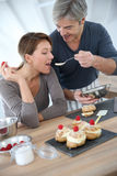 Woman tasting cake preparation made by her husband Stock Photo