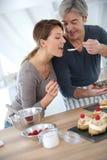 Woman tasting cake preparation Stock Images