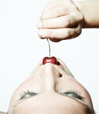 Woman Tasting A Cherry In Contrast Royalty Free Stock Photos