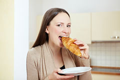 Woman tasting croissant Stock Photos