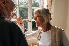Woman tasting the food prepared by her husband royalty free stock photos