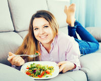 Woman tasting fresh green salad Stock Images