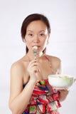 Woman tasting fruit salad Stock Image
