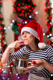 Woman tasting something tasty on Christmas Stock Image