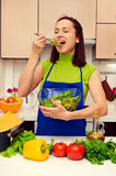 Woman tasting spoon of fresh salad in the kitchen Stock Photography