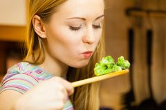 Woman tasting stir fry vegetable from pan. Woman in kitchen cooking stir fry frozen vegetables and tasting. Girl frying making delicious risotto. Dinner food royalty free stock images