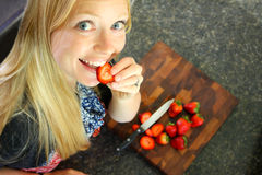 Woman Eating Strawberry While Slicing Fruit Stock Photos