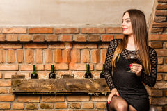 Woman tasting wine in rural cottage interior Royalty Free Stock Photo