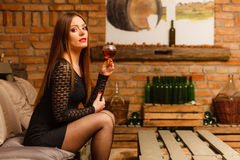 Woman tasting wine in rural cottage interior Royalty Free Stock Images