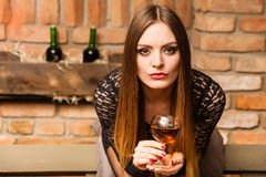 Woman tasting wine in rural cottage interior Stock Image