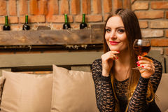Woman tasting wine in rural cottage interior Stock Photo