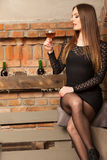 Woman tasting wine in rural cottage interior Stock Images