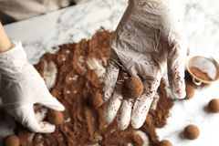 Woman with tasty chocolate truffles at table. Top view royalty free stock photography