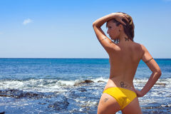 Woman with tatoo. Woman with yellow bikini near the blue sea with tribial tatoo stock images