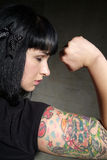 Woman with tattoo and fist. Black haired woman with tatoo clenches her fist Stock Image