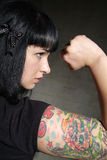 Woman with tattoo and fist Stock Photos