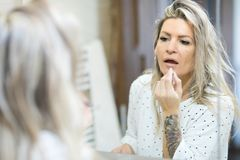 Woman applying morning make up in bathroom`s mirror stock image