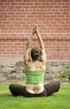 Woman with a Tattoo on Her Back Doing Yoga. Back of woman with a tattoo sitting on grass doing yoga stock images