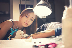Woman tattoo master during creation tattoo on a  hand under the lamp. Royalty Free Stock Photography