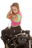 Woman tattoo motorcycle sit backwards look down. A woman with a tattoo is sitting on a motorcycle looking down over her shoulder stock photos