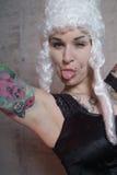 Woman with tattoo and peruke Stock Photography