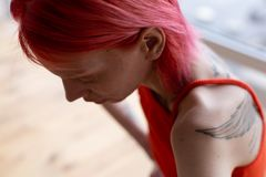 Woman with tattoo on shoulders and back feeling dizzy. Tattoo on shoulders. Red-haired anorexic woman with tattoo on shoulders and back feeling dizzy stock photos