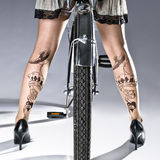 Woman with Tattooed Legs on a Bike Royalty Free Stock Photos