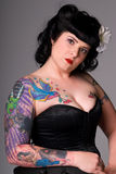 Woman with tattoos. Portrait of a woman with Pin-up style hair and make-up, wearing a black satin corset. She has lots of colorful tattoos all down her arm stock photo