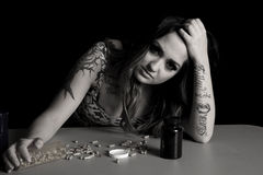 Woman with tattoos with drugs head tilted Stock Image