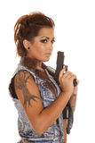 Woman tattoos holding a gun side. A woman with a gun and a tree tattoo on her arm stock photography