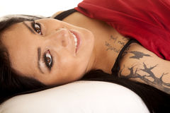 Woman tattoos lay red sheet smile. A woman in her bed laying with a smile on her lips and a red sheet over her body stock images