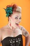 Woman with tattoos and pierced tongue. Happy Young Caucasian woman in bodice and unique hairdo stock images